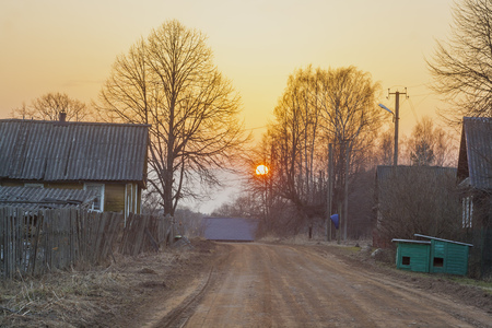 The sun over the village road in early spring