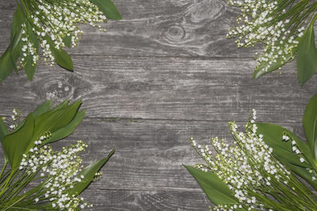 lily of the valley on a grunge rough wooden background postcard template