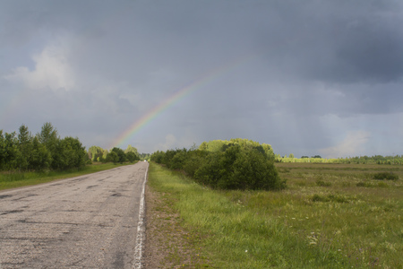 rainbow after storm over the rural road