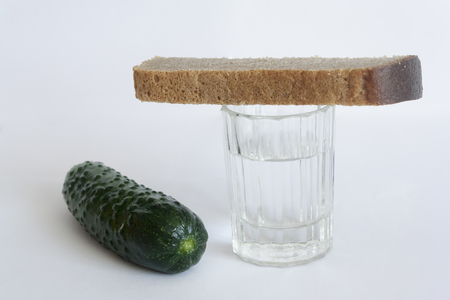 a stack of vodka, bread and salted cucumber on white background