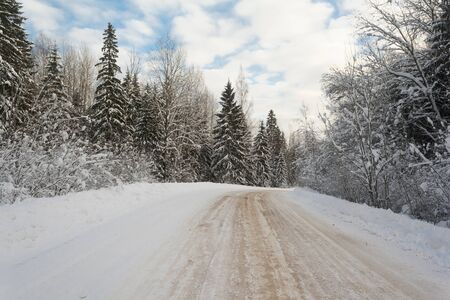 winter slippery road through the forest in the countryside