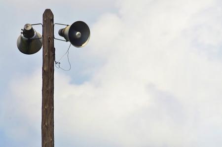 public address: Public address horn loud speakers on wooden pole over blue sky