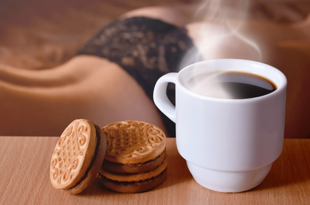 A cup of hot coffee and round cookies with a silhouette of a girl in black underwear in the background on a bed. Focus foreground priority. Small white coffee cup with steam and brown biscuits