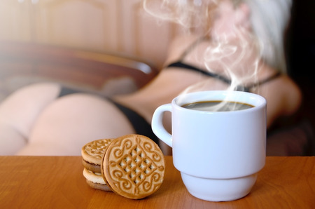 A cup of hot coffee and round cookies with a silhouette of a sexy girl in black underwear in the background on a bed. Focus foreground priority. Small white coffee cup with steam and brown biscuits