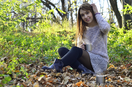 wench: Travel girl drinking from a mug on forest background. Girl on vacation enjoying the beauty of nature. Camping hiking lifestyle. Stock Photo