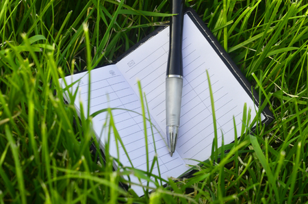 note booklet: White note-book with black pen and empty white pages on green grass field