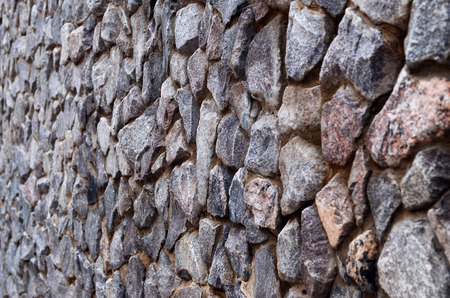 smeary: Background image of weathered stained thick and strong wall of rough stones of various shapes and sizes in perspective.