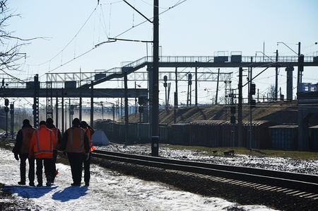 Several railway workers in signaling dirty orange uniforms are on the road next to the railway line. The train crew goes to work in the winter sunny morning.