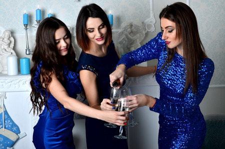 fill in: Three girls in blue dresses fill the glass of champagne to drink during the New Year celebrations. Drinking champagne at New Years Eve during the chimes. Warm and cozy Christmas atmosphere