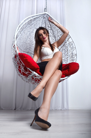 red pillows: Young beautiful girl in black dress and white lingerie resting in a sphere-like decorative swing with red pillows. The concept of whim elegant and cozy place to relax