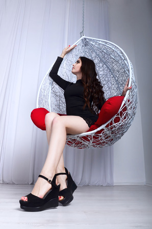 red pillows: Young beautiful girl in black dress and heels resting in a sphere-like decorative swing with red pillows. The concept of whim elegant and cozy place to relax