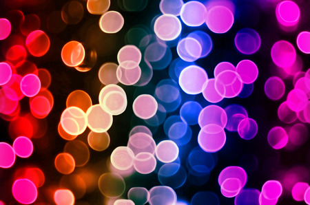 The artistic effect - blurred image of luminous objects. Background image bokeh. Colored balls of varying degrees of transparency on a dark background.