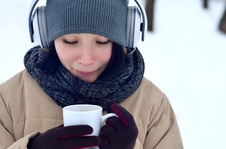 Beautiful pierced brunette caucasian young woman smiling while listening to music on large white headphones music and drink a cup of coffee in winter park or forest
