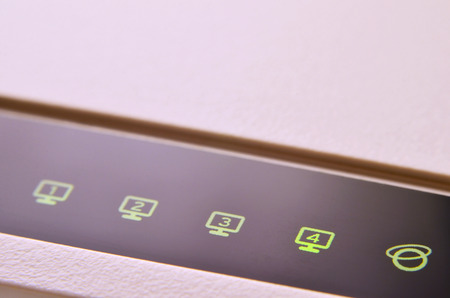 Closeup of internet router LED lights showing connection status. Emitting diode wireless on white plastic internet wi-fi cable modem