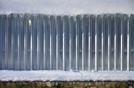 specular: The texture of shiny metal and embossed wall in broad daylight in the winter with a thick layer of snow on top of it.