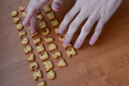 Mens fingers typing on the keyboard, which is composed of salty cracker in the form of letters and numbers. Simulating a computer keyboard using of cookies alphabet Stock Photo