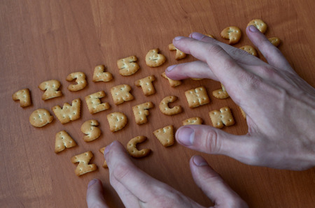 alphabet keyboard: Mens fingers typing on the keyboard, which is composed of salty cracker in the form of letters and numbers. Simulating a computer keyboard using of cookies alphabet Stock Photo
