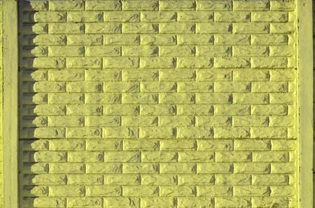 smeary: Stone fence texture - building feature. Texture of yellow concrete fence with relief and texture like a stone wall