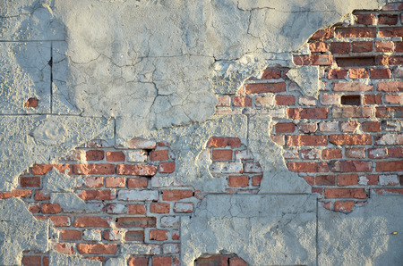 tension: Weathered stained brick wall with cracked cement tension