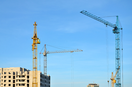 Working tall cranes inside place for with tall buildings under construction against a clear blue sky. Crane and building working progress with copyspace