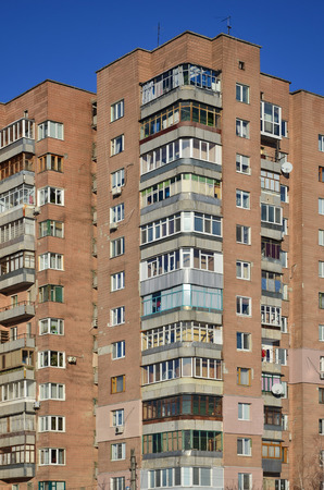 storey: Detailed photo of multi-storey residential building with lots of balconies and windows. Hostels for poor people in Russia and Ukraine in a damaged condition