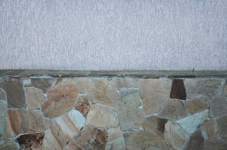formalization: Concrete wall texture with colored plaster. Beautiful design facade painted plaster walls with hand-made stone foundation.  Stock Photo