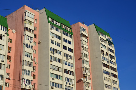 Multi-storey house with lots of windows, balconies and air conditioning. Detail photo of old skyscraper in Russia and Ukraine Stock Photo