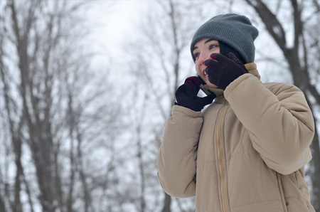 Beauty girl in winter forest. Beautiful young brunette caucasian pierced woman using smartphone in fashionable brown coat and warm grey hat