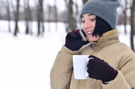 Portrait of pretty attractive caucasian pierced girl hipster in winter park. She is talking on modern smartphone and drink coffee. Youth street fashion. Walks in the open air