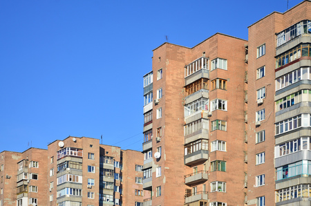 Detailed photo of multi-storey residential building with lots of balconies and windows. Hostels for poor people in Russia and Ukraine in a damaged condition
