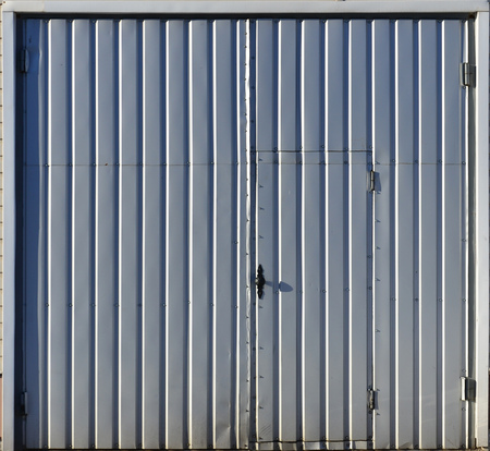 Stock Photo   The Texture Of Brown Corrugated Metal Door With A Colored  Frame. The Texture Street Gate Of Iron Sheets, Fortified With Small Screws.