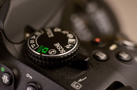 Close-up macro shot of a modern digital SLR camera. Detailed photo of black camera body with buttons to control and switch shooting modes Stock Photo
