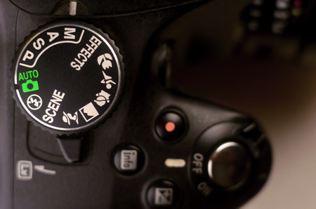 Close-up macro shot of a modern digital SLR camera. Detailed photo of black camera body with buttons to control and switch shooting modes Foto de archivo