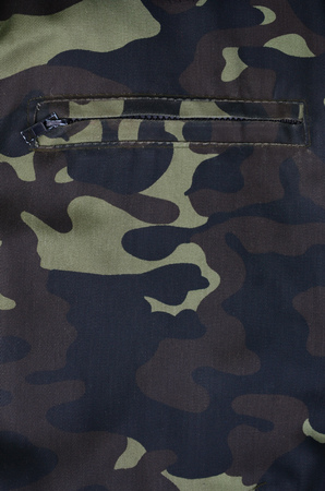 dark olive: Texture of fabric with a camouflage painted in colors of the marsh with pocket. Army background image. Textile pattern of military camouflage fabric