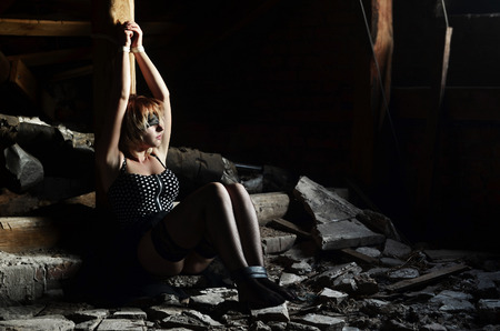 Tied to a wooden pole girl sitting in an old attic of an abandoned building. The concept of violence, rape and criminal use of people as hostages, restricting their freedom
