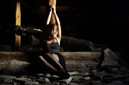 Tied to a wooden pole girl sitting in an old attic of an abandoned building. Beautiful young blonde girl in a black dress and stockings as a hostage with his hands tied