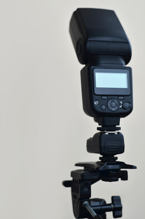 tripod mounted: External photographic flashlight gun is mounted on the remote wireless control radio trigger set, which stands on a tripod. lighting equipment for studio photography on beige background