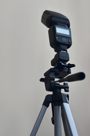tripod mounted: External photographic speedlight gun is mounted on the multichannel sync trigger set on a tripod. lighting equipment for studio photography. Set of professional photographer
