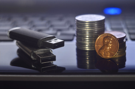 USB memory cards and a few coins lying on the body of black laptop in front of his keyboard. Virtual memory storage with USB output and a small amount of money