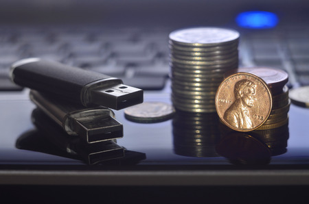 USB flash cards lying on black laptop case in front of his keyboard. The concept of earning on the Internet, online monetization and payment of virtual work Stock Photo