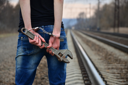 The girl in handcuffs with the adjustable wrench on the railway track background. The concept of crime prevention with the participation of the railway and trains. Evening photo of the lower half of the body of a girl with handcuffed hands