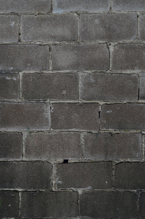 Weathered stained old block wall background. Texture of an old wall of several floors with lots of rows of blocks