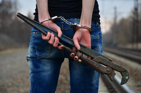 The girl in handcuffs with the pipe wrench on the railway track background. The concept of crime prevention with the participation of the railway and trains. Evening photo of the lower half of the body of a girl with handcuffed hands
