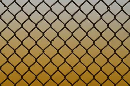 dirty car: Texture of an old and rusty metal mesh on a neutral colored background. A sad and gloomy image with a flat fencing net used in prisons or industrial plants