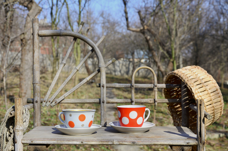 A rustic still-life with a cups of tea and a straw hat on a wooden hand-made shelf made from old dried bamboo. Cups of hot tea in the courtyard of the spring garden. Concept of a pleasant holiday at the cottage in the village