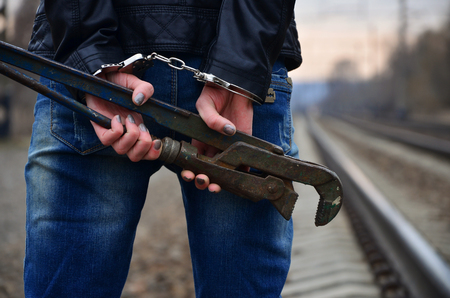 handcuffs: The girl in handcuffs with the pipe wrench on the railway track background. The concept of crime prevention with the participation of the railway and trains. Evening photo of the lower half of the body of a girl with handcuffed hands