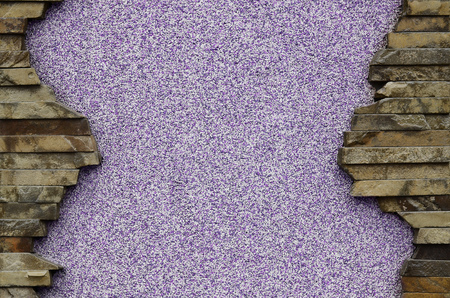 Plastered and treated violet concrete wall with a beautiful frame of flat rectangular stones. Procurement for slides, presentations or tables with a huge amount of free space for your text and images