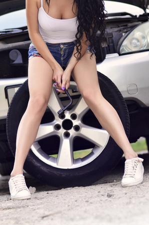Young and sexy girl in light t-shirt and blue denim shorts with wheel wrench are sitting on the big and silvery car wheel Imagens