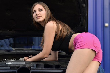 Young cute girl in pink shorts and black shirt with wrenches near a black car with an open hood. The concept of repair and maintenance of a car in the performance of a girl-mechanic Reklamní fotografie