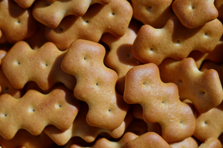 A huge bunch of salted biscuits of small sizes close-up. Macro shot of a large amount of salt cracker in golden yellow tones